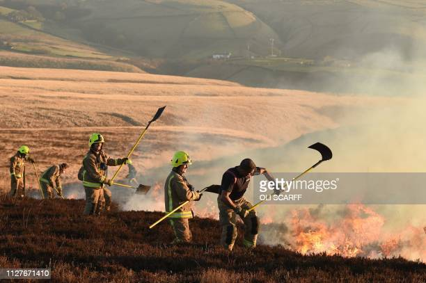 Firefighters tackle a blaze on moorland above Marsden northwest England on February 27 2018