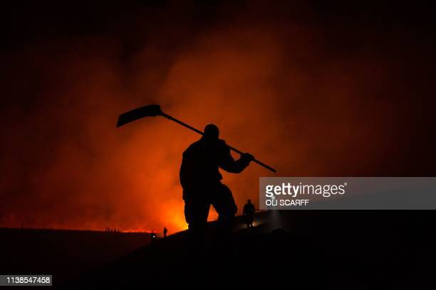 TOPSHOT Firefighters tackle a blaze on moorland above the village of Marsden northwest England on April 21 2019