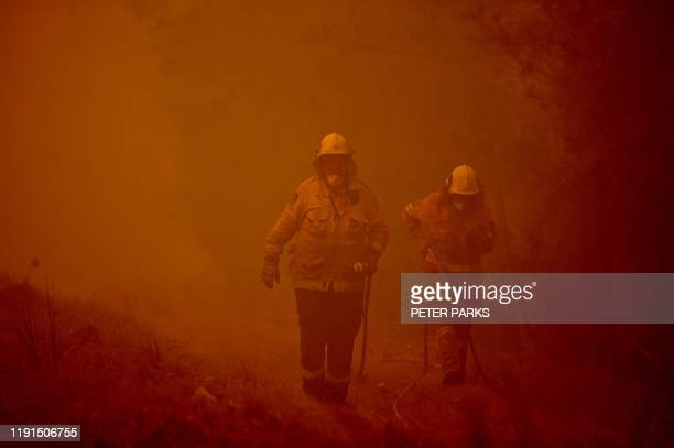 TOPSHOT Firefighters tackle a bushfire in thick smoke in the town of Moruya south of Batemans Bay in New South Wales on January 4 2020 Up to 3000...