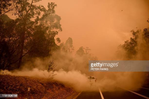 Firefighters tackle a bushfire in thick smoke in the town of Moruya, south of Batemans Bay, in New South Wales on January 4, 2020. - Up to 3,000...