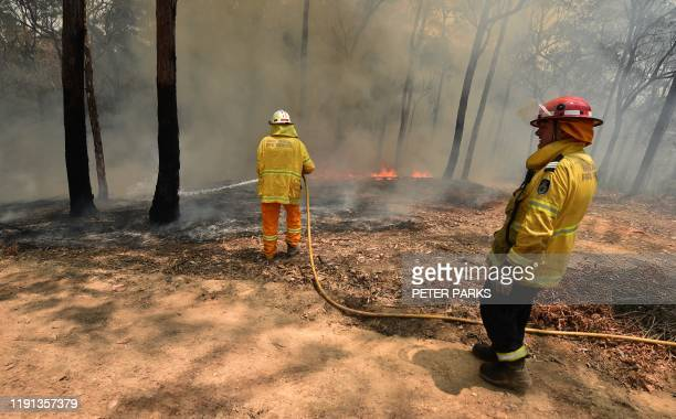 Firefighters tackle a bushfire near Batemans Bay in New South Wales on January 3 2020 With temperatures expected to rise well above 40 degrees...