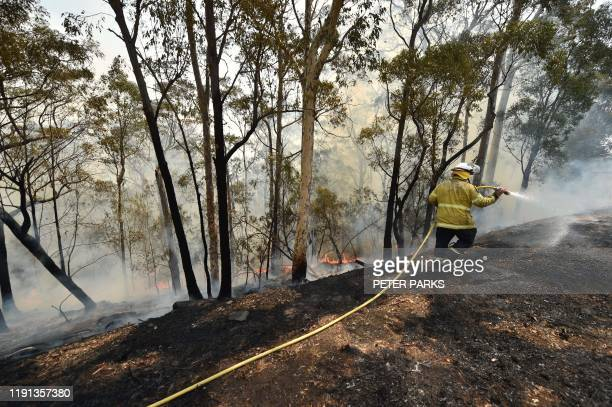 Firefighters tackle a bushfire near Batemans Bay in New South Wales on January 3, 2020. - With temperatures expected to rise well above 40 degrees...