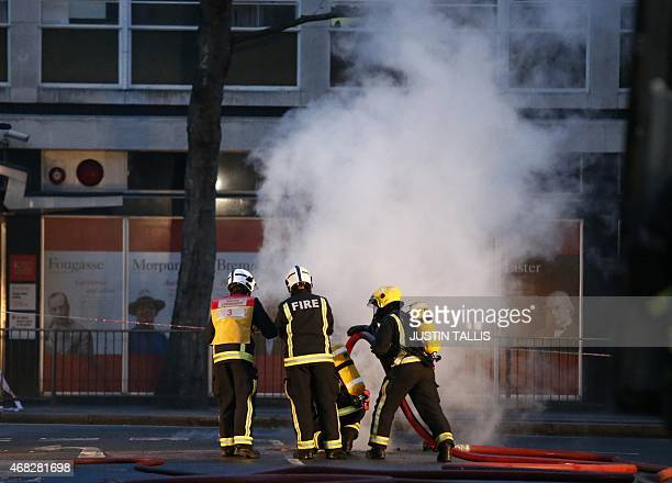 Firefighters tackle a fire under Kingsway in the west end of London on April 1 2015 Firefighters believe the blaze started among cables underground...