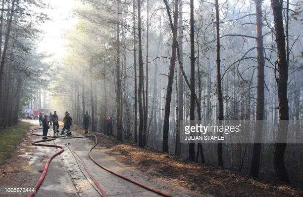 Firefighters tackle a forest fire near Potsdam eastern Germany on July 26 2018 Dozens of wildfires have hit countries across northern Europe and...