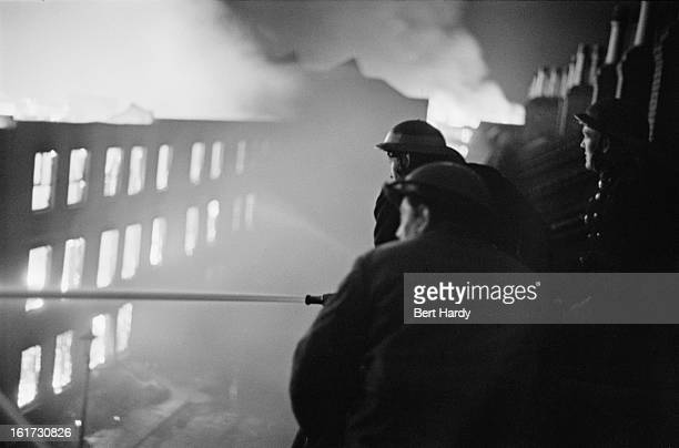 Firefighters tackling a blaze from the roof of a building across the street during the Blitz London 1941 Original publication Picture Post 587...