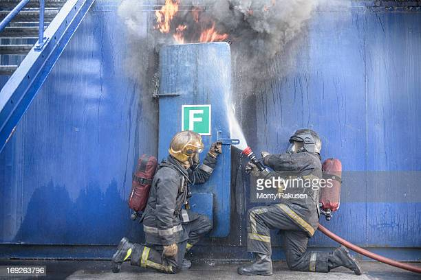 Firefighters tackling flames behind steel door in fire simulation training facility