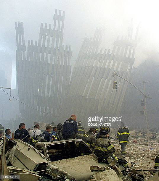 Firefighters take a break at the remains of the twin towers of the World Trade Center in lower Manhattan 11 September in New York after two planes...