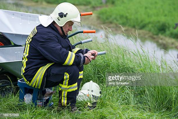 A firefighters takes a break on the top of a dyke after strengthen it against the rising Gera river and to prevent flooding on June 1 2013 near...