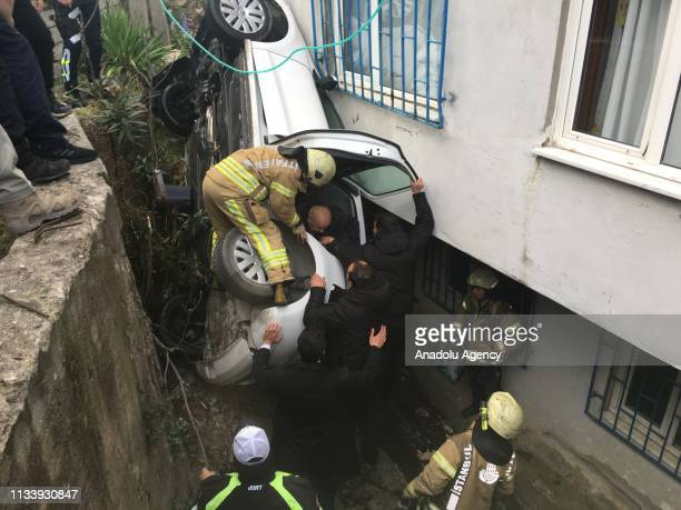 Firefighters team help a man to get out of a car after the driver lost control of the car and it fell in a hole between a sustaining wall and a...