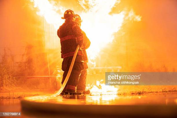 firefighters team - burning stock pictures, royalty-free photos & images