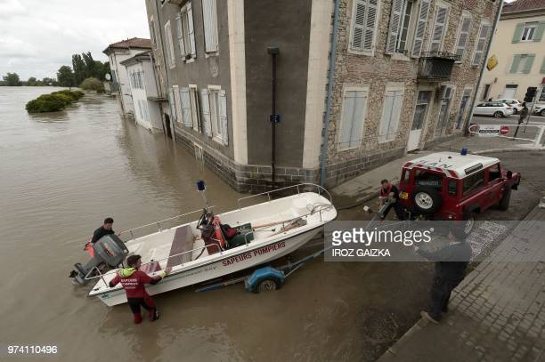 Firefighters trailer their boat in a flooded street on June 14 2018 following heavy rains in Peyrehorade in the region of Landes France