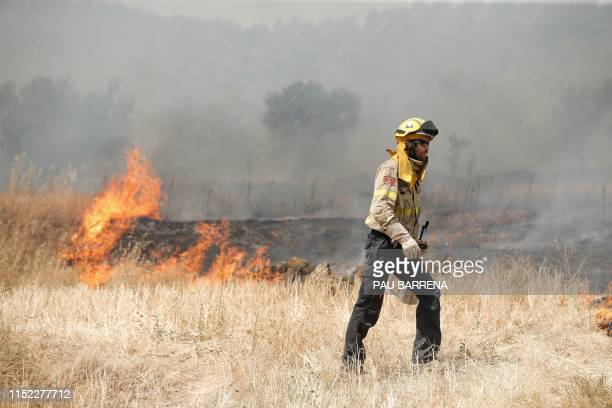 Firefighters tries to extinguish a fire near Flix on June 27, 2019 as a forest fire raged out of control in the northeastern region of Catalonia and...