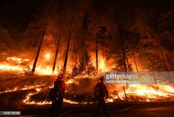 Firefighters try to control a back burn as the Carr fire continues to spread towards the towns of Douglas City and Lewiston near Redding California...