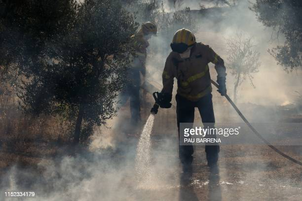 Firefighters try to control a forest fire raging near La Torre de l'Espanyol in the northeastern region of Catalonia on June 27 2019 A Spanish forest...
