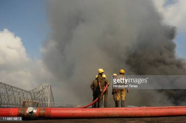 Fire-fighters try to douse the fire that broke out at a chemical godown near Howrah Bridge, adjacent to Jagannath Ghat, on June 8, 2019 in Kolkata,...