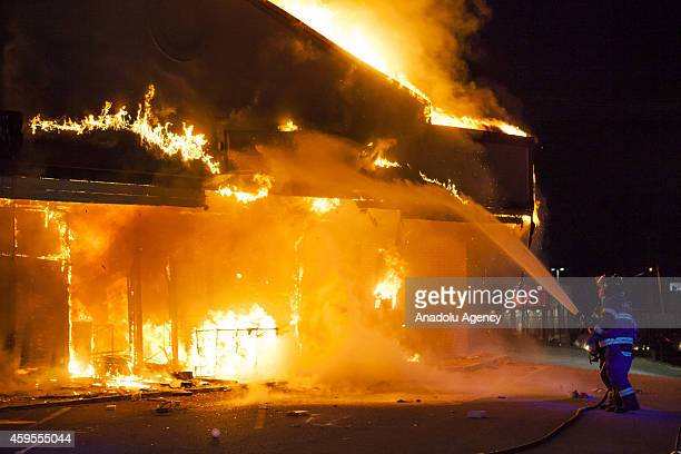 Firefighters try to extinguish a burning building set on fire by protestors after grand jury's decision not to indict a police officer Darren Wilson...