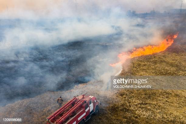 Firefighters try to extinguish a field fire burning at a 30kilometer Chernobyl exclusion zone not far from the nuclear power plant on April 10 2020