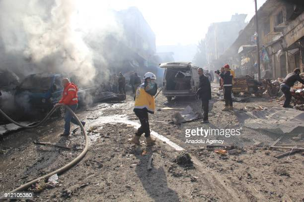 Firefighters try to extinguish a fire at a marketplace after an airstrike in the deescalation zone of Eriha district of Idlib Syria on January 30...