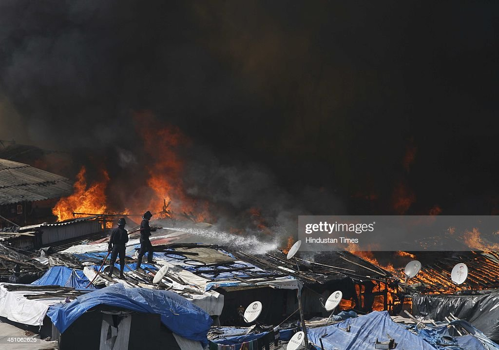 Firefighters try to extinguish a fire at Ambedkar Nagar slum, Cuffe Parade on November 21, 2013 in Mumbai, India. Several huts were gutted in a fire that broke out in the settlement. About 10 fire engines and eight water tankers have been rushed to the spot to douse the flames.