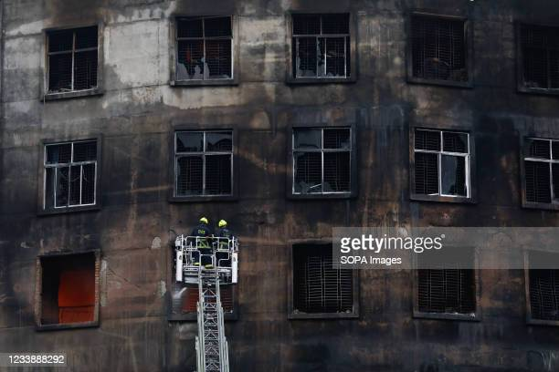 Firefighters try to extinguish a fire inside the building after a fire broke out at a factory named Hashem Foods Ltd in Rupganj of Narayanganj...