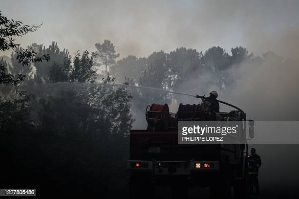 Firefighters try to extinguish a fire near Le Tuzan southeastern France after a wildfire destroyed more than 150 hectares of pine trees in southern...