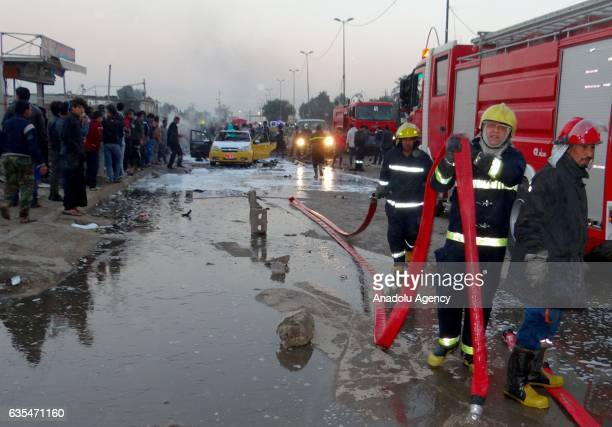 Firefighters try to extinguish fire at the site of a suicide car bomb attack in the eastern Habibiya neighborhood of Baghdad Iraq on February 15 2017...