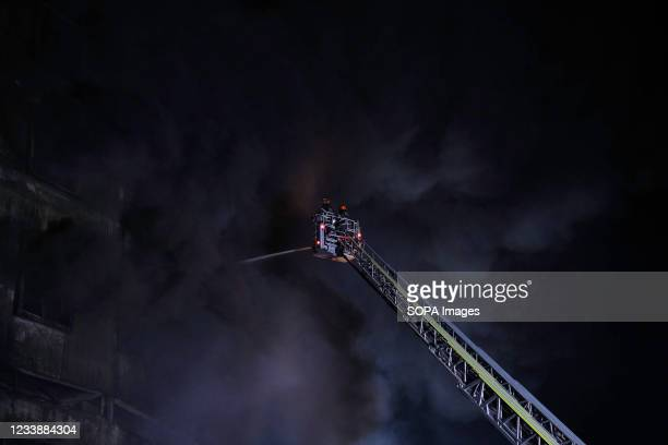 Firefighters try to extinguish fire inside the building after a fire broke out at a factory named Hashem Foods Ltd in Rupganj of Narayanganj district...
