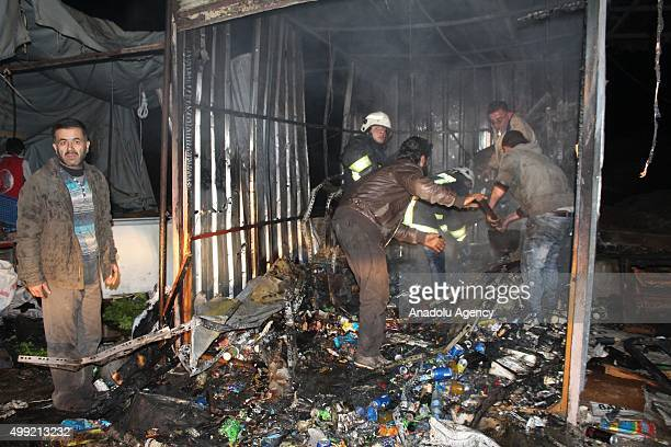 Firefighters try to extinguish fire on burning vehicles following the Russian airstrikes on November 29 2015 in Azaz town of Aleppo Syria Casualties...