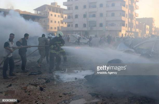 Firefighters try to extinguish the fire after an attack with a bombladen vehicle in AlDana district of Idlib Syria on June 24 2017