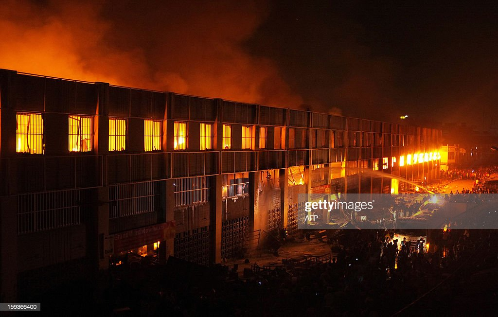 Firefighters try to extinguish the Lome's Grand Marche (Lome Big Market), where cloth sellers and other vendors sell their goods, late on January 11, 2013 in Lome. Crowds of people filled the streets surrounding the multi-storey structure, as a few vendors entered the burning building to save their goods. AFP Photo / Daniel Hayduk
