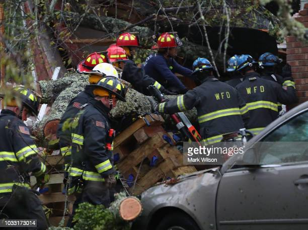 Firefighters try to gain access to 3 people in a home that a large tree fell on after Hurricane Florence hit the area on September 14 2018 in...