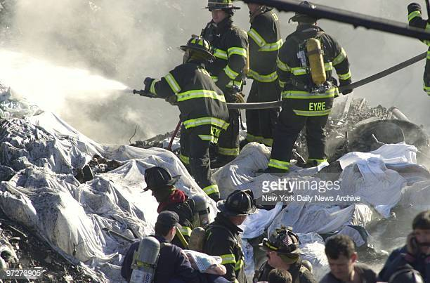 Firefighters try to get fire under control and look for victims in the smoldering remains of American Airlines flight 587 after it crashed in the...