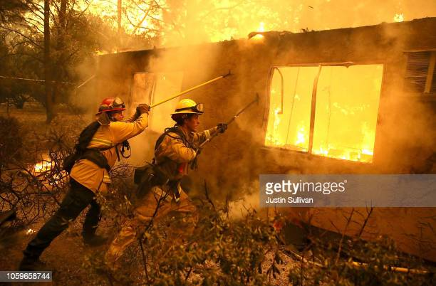Firefighters try to keep flames from burning home from spreading to a neighboring apartment complex as they battle the Camp Fire on November 9, 2018...