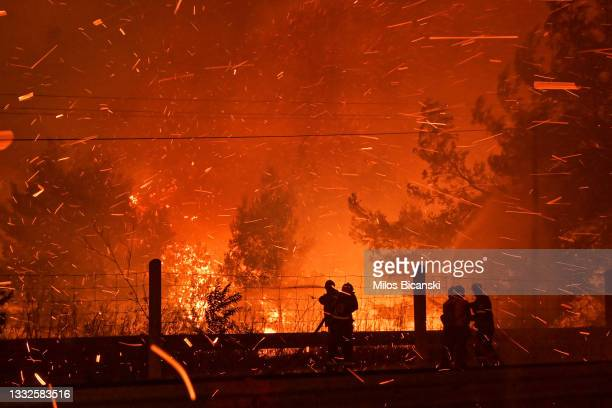 Firefighters try to put out a fire as flames spread over a highway during a wildfire on August 5 2021 in northern Athens, Greece. People were...