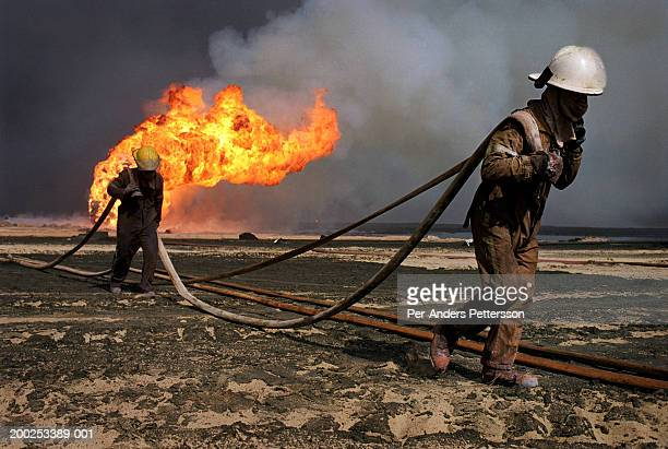 Firefighters try to put out a fire at Burham oilfield, Kuwait