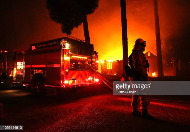 Firefighters try to save a building as the Camp Fire moves through the area on November 8 2018 in Paradise California Fueled by high winds and low...