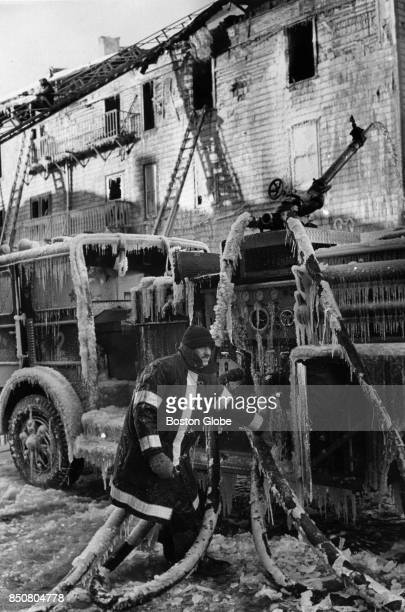 Firefighters try to shut down frozen valves after a fouralarm fire ripped through a vacant apartment building at Andrew Square in Boston Jan 12 1981