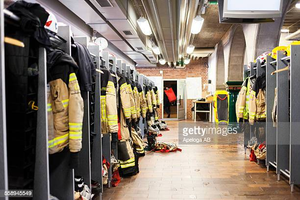 firefighters uniforms hanging in fire station - fire station stock photos and pictures