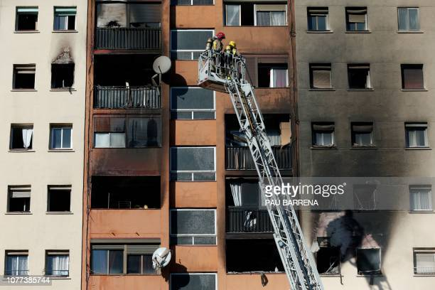 Firefighters use a fire truck ladder to reach the different floors of an apartment building after a fire broke out in Badalona near Barcelona on...