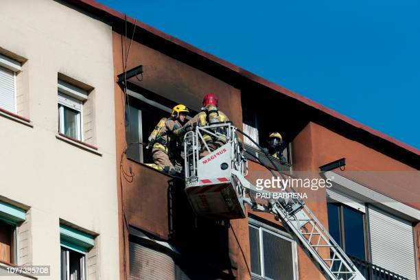 Firefighters use a fire truck ladder to reach the top floor of an apartment building after a fire broke out in Badalona near Barcelona on January 5...