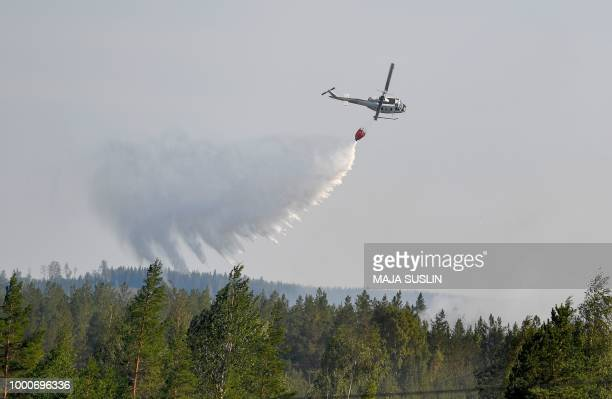Firefighters use a helicopter to try to put out forest fires near Ljusdal Sweden on July 17 2018 / Sweden OUT