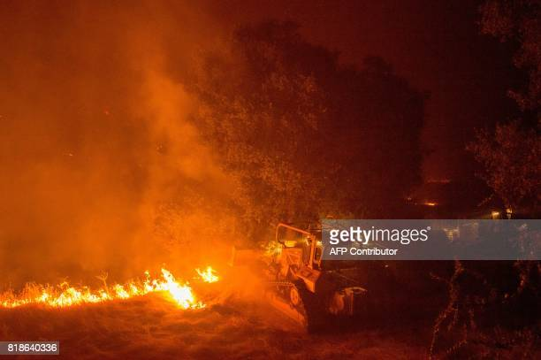 Firefighters use bulldozers to bury flames from the Detwiler fire near the town of Mariposa California on July 18 2017 California has suffered...