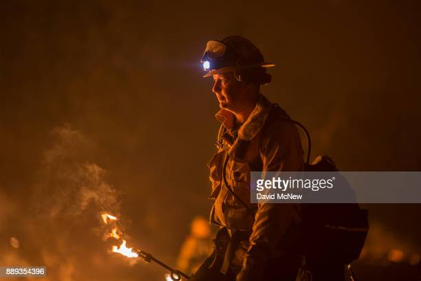 Firefighters use drip torches to set a backfire at night in an effort to make progress against the Thomas Fire before the winds return with the...