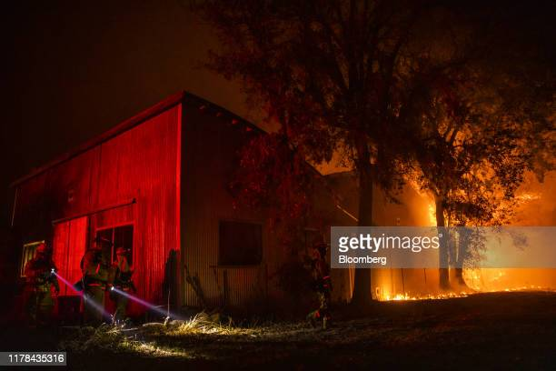 Firefighters use flashlights to search the perimeter of a building at the Soda Rock Vineyards during the Kincade fire in Healdsburg California US on...