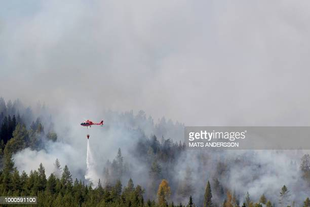 Firefighters use helicopters to fight wildfires outside Hammarstrand in Sweden on July 16 2018 Due to the dry weather 80 wildfires burned in Sweden /...
