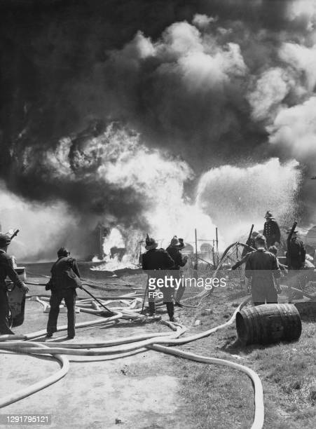 Firefighters use hoses to tackle a blaze at the British Cellulose factory in Sydenham, south-east London, England, 28th April 1948. More than 1,000...