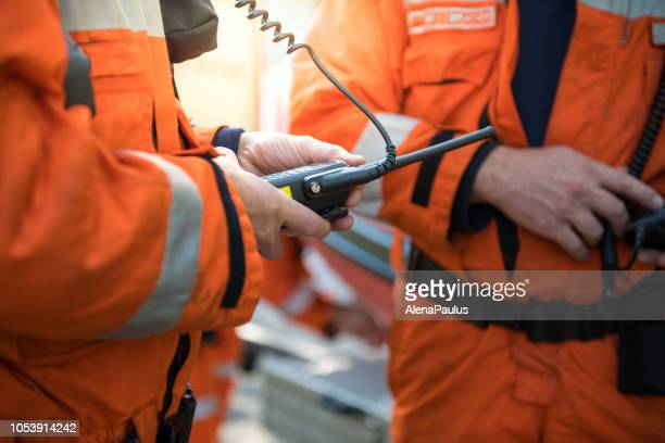 firefighters using walkie talkie, rescue operation close up - radio stock pictures, royalty-free photos & images