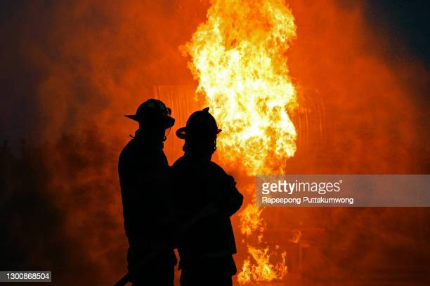 firefighters using water to fighting with the fire flame from oil to control fire not to spreading out. - firefighter stock pictures, royalty-free photos & images