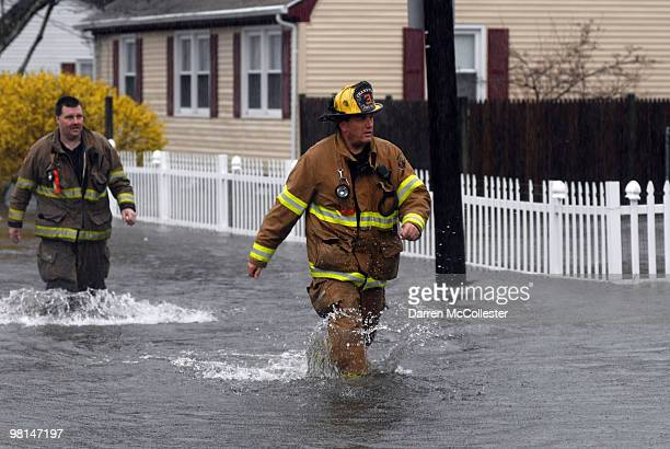 Firefighters wade in knee deep water due to flooding from the Pawtuxet River on Moore and Perkins Street March 30 2010 in attempts to help local...