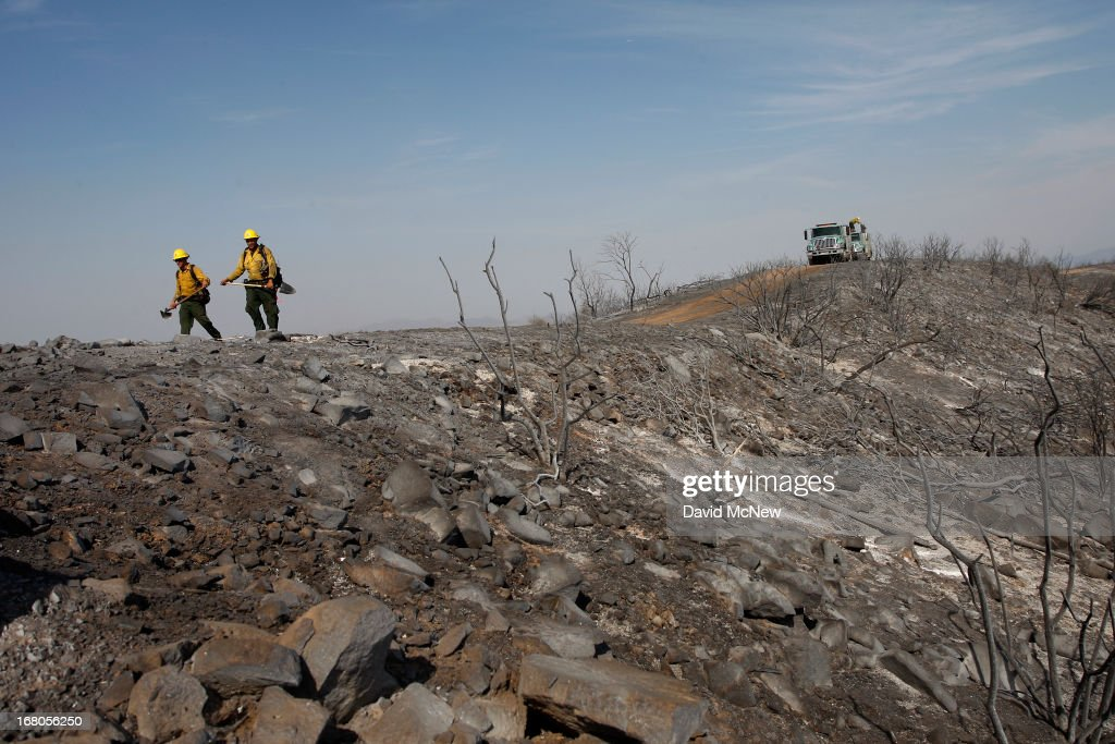 Firefighters walk a charred ridge at the Springs fire on May 4, 2013 near Camarillo, California. Improving weather conditions are helping firefighters get the upper hand on the wildfire which has grown to 28,000 acres and is now 56 percent contained.
